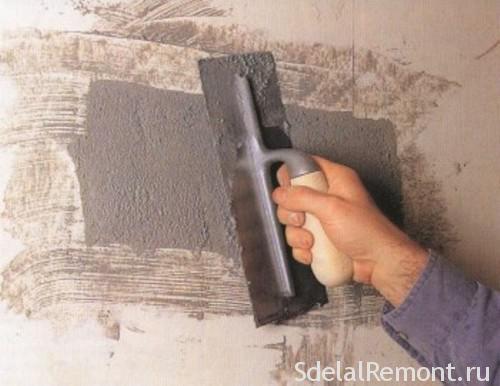Замазывание дырки в стене шпателем