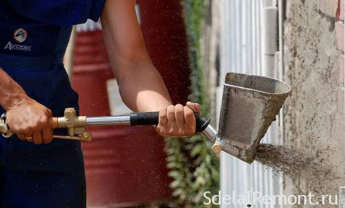 Использование ковша для распыления штукатурки на стену