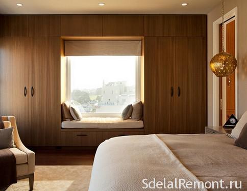 Шкафы вокруг окна в спальне