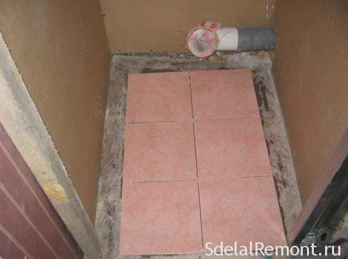 laying tiles on the floor in the toilet