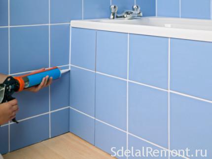 Рукі нанясенне герметыка на бок ванны
